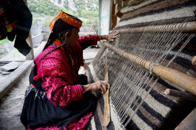何かを編むカラーシャの女性