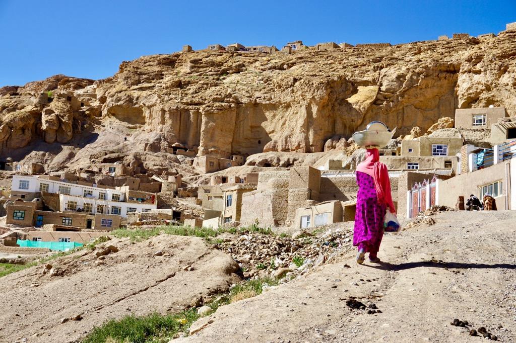 食器を洗い終えて丘を上る女性